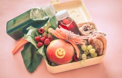 Breakfast or lunch with healthy food in a yellow box, on a pink royalty free stock image