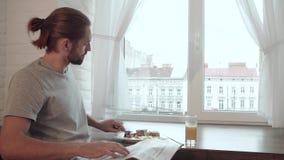 Breakfast. Man Reading Newspaper, Drinking Juice And Eating Food