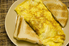 Breakfast meal. Omelette and white toast on a tan plate on a wicker placemat Royalty Free Stock Images