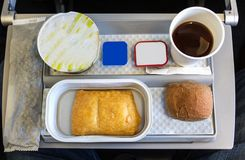 A breackfast meal on a tray in the economy class cabin of an air. A breakfast meal with coffee, butter, bread and yogurt on a tray, onboard a short flight in Royalty Free Stock Photo