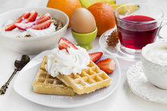 Breakfast meal with waffles, cream and strawberries, fresh fruit Stock Image