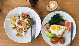 Breakfast meals with eggs, fish and vegetables on plates near cups of coffee and ice cola