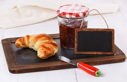 Breakfast menu with croissant and jam over white wooden backgrou. Nd stock image