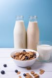 Breakfast with milk and cereals with blueberries with bottles on a background on a wooden white table. Vertical shot Royalty Free Stock Photography