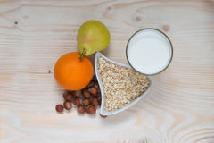 Breakfast milk, fruit, nuts, pear and orange. Desk, breakfast a glass of milk and fruit Stock Photography