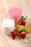 Breakfast with milk, strawberry smoothie and afternoon snack. Glass of strawberry smoothie with milk and afternoon snack on wood of fir Stock Images