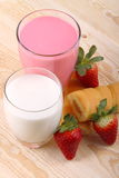 Breakfast with milk, strawberry smoothie and afternoon snack. Glass of strawberry smoothie with milk and afternoon snack on wood of fir Stock Photography