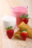 Breakfast with milk, strawberry smoothie and afternoon snack. Glass of strawberry smoothie with milk and afternoon snack on wood of fir Stock Image