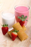 Breakfast with milk, strawberry smoothie and afternoon snack. Glass of strawberry smoothie with milk and afternoon snack on wood of fir Royalty Free Stock Image