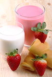 Breakfast with milk, strawberry smoothie and afternoon snack. Glass of strawberry smoothie with milk and afternoon snack on wood of fir Royalty Free Stock Photo