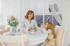 Breakfast mom and daughters. In the same pajamas. stock image