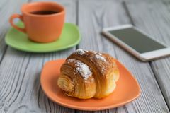 Breakfast of coffee and a croissant on a wooden table, a mobile phone is next to each other. Breakfast in the morning on a wooden background, coffee, croissant Stock Images