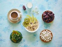 Breakfast with muesli on turquoise background. Muesli with Turkish sweets, kiwi, dates and milk. Breakfast with muesli on blue background. Muesli with Turkish royalty free stock photos
