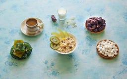 Breakfast with muesli on turquoise background. Muesli with Turkish sweets, kiwi, dates and milk. Breakfast with muesli on blue background. Muesli with Turkish stock photography