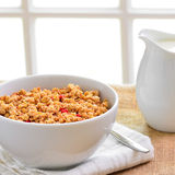 Breakfast Muesli cereal clusters with a jug of fresh milk. Royalty Free Stock Photography