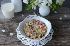 Breakfast: muesli with a glass of milk and a bouquet of blooming apple tree branches royalty free stock photo