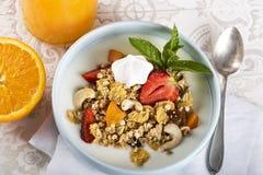 Breakfast. Muesli with milk or yogurt, nuts and strawberries, orange juice and orange.  stock photos