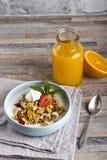 Breakfast. Muesli with milk or yogurt, nuts and strawberries, orange juice and orange.  stock photography