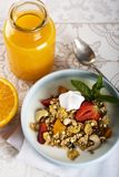 Breakfast. Muesli with milk or yogurt, nuts and strawberries, orange juice and orange.  royalty free stock photography