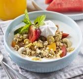 Breakfast. Muesli with milk or yogurt, nuts and strawberries, orange juice and watermelon.  stock photos