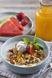 Breakfast. Muesli with milk or yogurt, nuts and strawberries, orange juice and watermelon. / royalty free stock photography