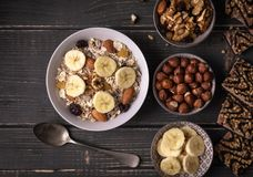 Breakfast with muesli in white bowl on gray natural desk with nuts and bananas around. Some cookies on the right side Stock Photo