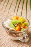 Breakfast with muesli, yoghurt, tropical fruits Stock Images