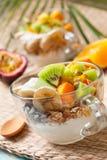 Breakfast with muesli, yoghurt, tropical fruits Stock Photography