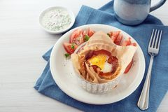 Breakfast muffin with egg and bacon in toasted bread, tomato, ch Stock Photo
