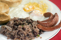 Breakfast in Nicaragua gallo pinto eggs sausage. Typical breakfast in Nicaragua gallo pinto rice beans sausage eggs and toast as photographed in Corn Island stock image