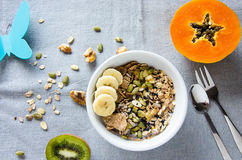 Breakfast with nuts, papaya and kiwi with a plastic butterfly Stock Images