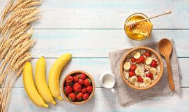 Breakfast with oat flakes and  natural milk, fresh banana, straw Royalty Free Stock Photos