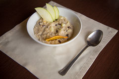Breakfast Oatmeal with apple, raisins, dry orange on the table. With a napkin and spoon Royalty Free Stock Photo