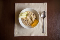 Breakfast Oatmeal with apple, raisins on the table. With a napkin and spoon Royalty Free Stock Image