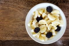 Breakfast oatmeal with bananas and blackberries over wood Stock Photo