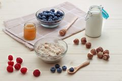 Breakfast of oatmeal with blueberries, raspberries, honey, milk and hazelnuts.  Royalty Free Stock Photography