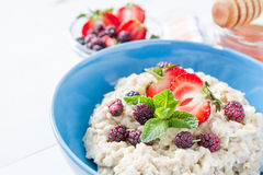 Breakfast - oatmeal with honey and berries, blue bowl Royalty Free Stock Photos