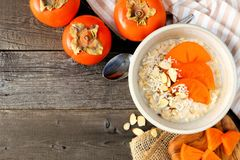 Breakfast oatmeal with persimmons overhead on wood Royalty Free Stock Image