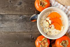 Breakfast oatmeal with persimmons overhead on wood Royalty Free Stock Images