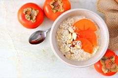 Breakfast oatmeal with persimmons on a marble background Royalty Free Stock Image