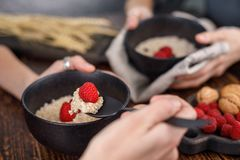 Breakfast from oatmeal porridge with blueberries and fresh raspberries. Still life on a wooden background with hands. Side view, close-up Stock Photos