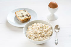 Breakfast: oatmeal porridge, egg and slice of cake Royalty Free Stock Photography