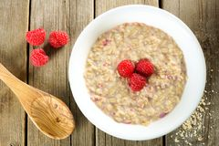Breakfast oatmeal with raspberries against wood Stock Photography