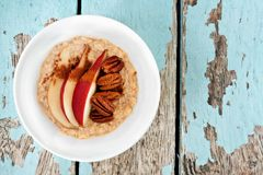 Breakfast oatmeal with red pear, pecans, above view on wood Stock Images