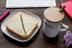 Breakfast in office with cocoa and sandwich on wooden desk Stock Image