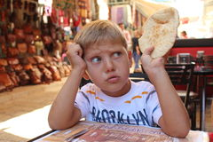 Breakfast in old city market in Jerusalem. Picture of a little boy, travel child,  seating in a street cafe in old city market in Jerusalem and taking a lazenge Royalty Free Stock Image