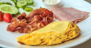 Breakfast with Omelette, Bacon, Ham, and Salad. Omelette on top with cheese, bacon, ham, and salad Stock Photos