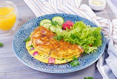Breakfast. Omelette with radish, red onion and fresh salad on blue plate. royalty free stock images