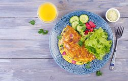 Breakfast. Omelette with radish, red onion and fresh salad on blue plate. Frittata - italian omelet. Top view stock photos
