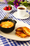Breakfast. Omelette with tomatoes, toasted bread and strawberries. Healthy breakfast. Omelet in a black ceramic cup.toasted bread, strawberries and a cup of tea Stock Photo